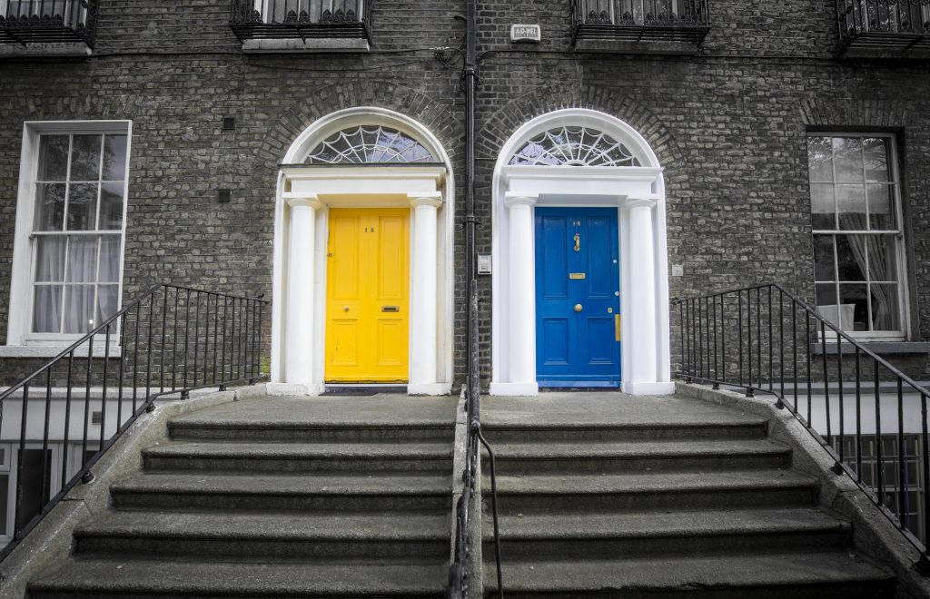 An image of two front doors, one which has been painted in blue and the other in yellow.