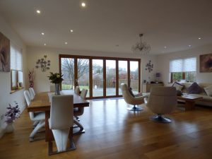 An image of bi-folding doors in an open plan living and dining area, leading out into the garden.